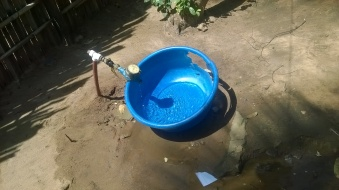 Water collection from communal tap. Natite, Pemba.